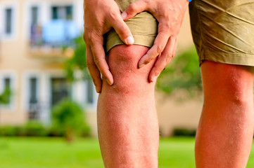 man holding hands sore knee