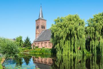 Dutch church at a river in summer