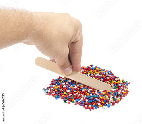 Colorful plastic polymer granules and man hand on white