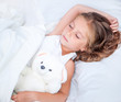 little girl  in the  bed with teddy bear
