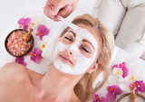 Cosmetician Applying Facial Mask On Face Of Woman poster