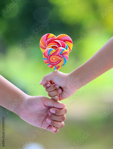 Two hand hold lollipop on green background