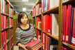 Thai college girl is holding stack of books .