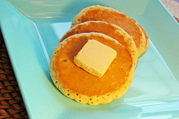 Three pancakes with a pat of butter