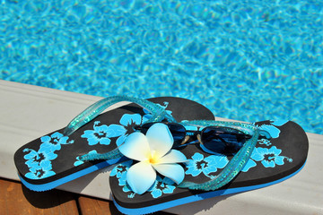 Flip flops on the edge of a pool