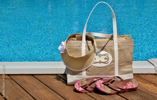 Beach bag with flip flops and a sun visor sitting on a pool deck