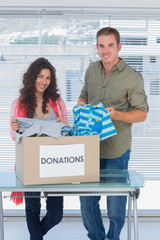 Smiling volunteers taking out clothes from a donation box