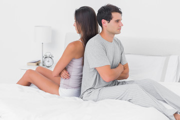 Couple ignoring each other sitting back to back on bed