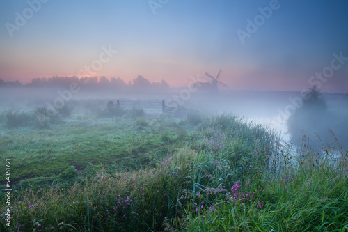 dense morning fog and windmill