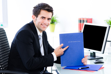 junger mann zeigt auf bewerbungsmappe