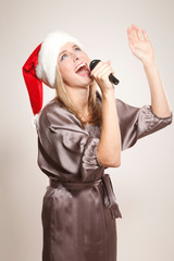 Girl in Santa hat singing in microphone