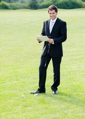 lächelnder geschäftsmann mit tablet auf golfplatz