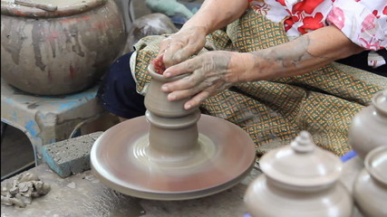 Close up of hands making earthen jar on a wheel