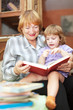 grandmother and girl reads book