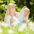 Happy mother and daughter blowing bubbles in the park