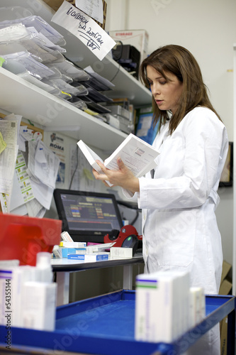 Beautiful female pharmacist controlling medicine in pharmacy