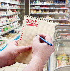 hand holds a notepad with diet plan