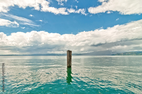 wooden pole in lake Garda with cloudy sky