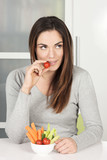 Beautiful girl eating vegetables