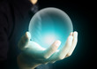 Hand holding a glowing crystal ball - 54359715