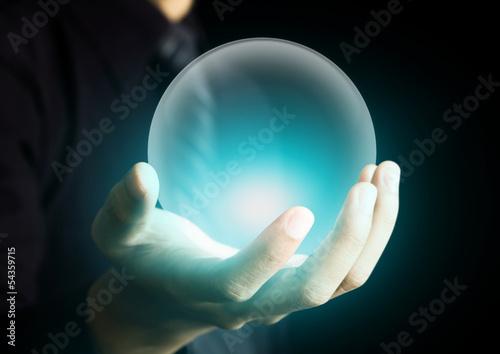 Leinwandbild Motiv Hand holding a glowing crystal ball