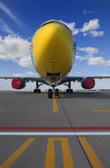 Yellow commercial airplane parked on an airfield