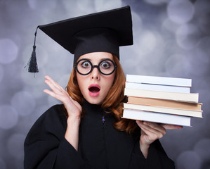 graduating student girl in an academic gown with books