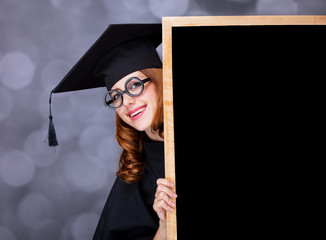 graduating student girl in an academic gown near blackboard
