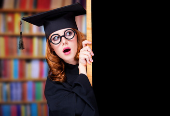 graduating student girl in an academic gown near blackboard