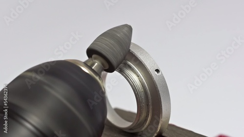 Grinding metal part with sharp tip.