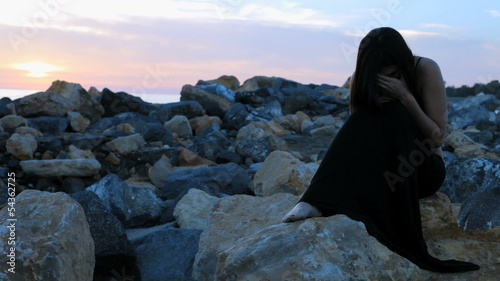 Woman desperate sitting on rocks feeling lonely