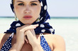 beautiful blond woman in blue shawl on beach