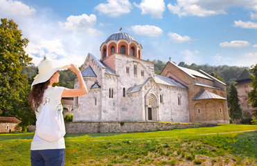 Beautiful young woman in front of Monastery Studenica, Serbia.