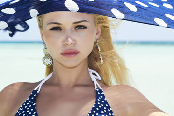 beautiful woman with blue shawl on a beach