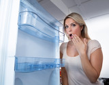 Woman Looking In Empty Fridge