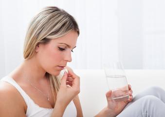 Portrait of woman taking pills