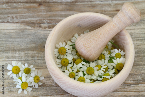 Chamomile flowers in wooden mortar with copy space