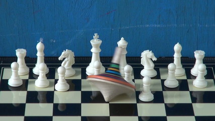 colorful whirligig in motion on chessboard with chessmens