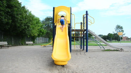 Child Playing in a Slide in a Playground