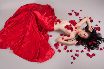 Girl in a red dress lying in rose petals