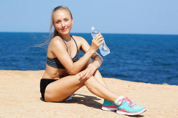Fitness woman with water after running at beach