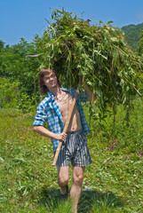 Young man carrying hay