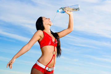 sport girl in red uniform with a bottle of water