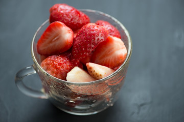 Ripe sliced strawberries in a cup, horizontal shot