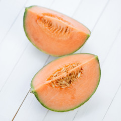Two cantaloupe slices on wooden boards, view from above