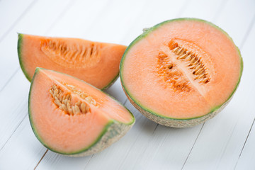 Sliced cantaloupe melon on wooden boards, studio shot