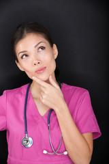 Doctor / medical female nurse thinking looking up