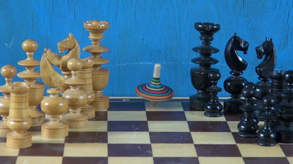 colorful wooden whirligig in motion on chessboard with chessmen
