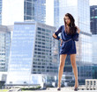Sexy woman in a blue dress is stretching near skyscrapers