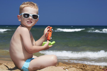 child in sunglasses on the beach. little boy near the sea